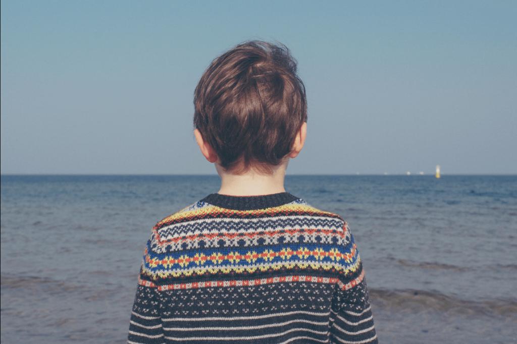 Niño de espaldas con el mar de fondo