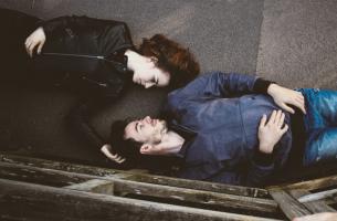 pareja tumbada en el suelo mirándose