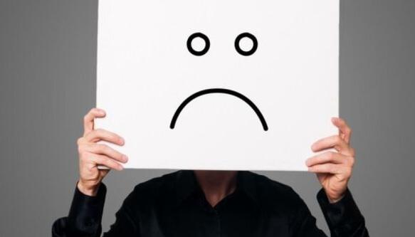 persona-sujetando-una-cartulina-blanca-enfrente-de-su-cara-con-una-cara-triste-dibujada