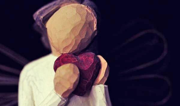Mujer con un corazón en la mano llorando la ruptura de pareja