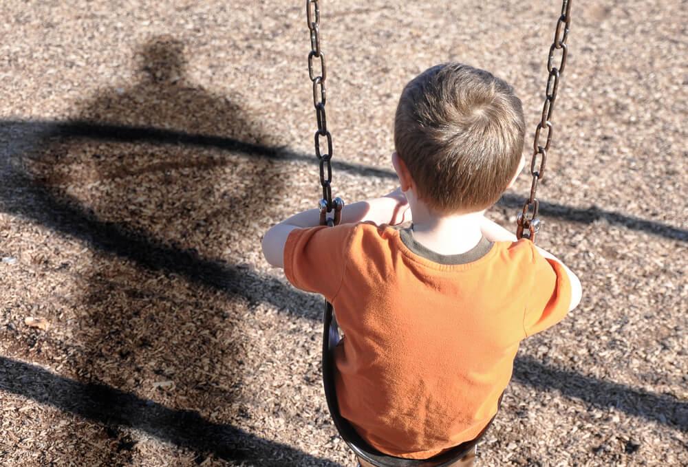 Niño sentado en un columpio con miedo