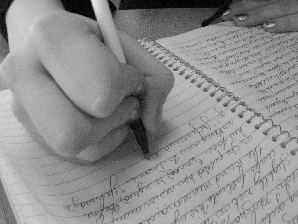 Mujer escribiendo para un estudio de grafología
