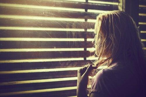 Mujer mirandopor la ventana guardando sus emociones
