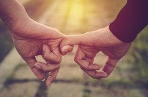 Pareja con dedos unidos mostrando amor