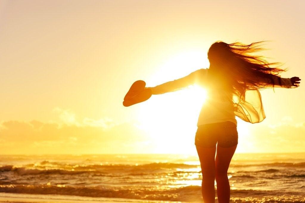 Mujer con un corazón en su mano mirando al mar
