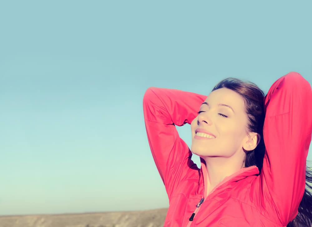 Mujer feliz echándose el pelo hacia atrás