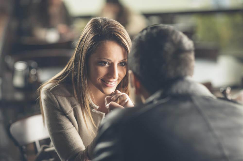 Mujer mirando a un hombre preguntándose si está interesado en ella
