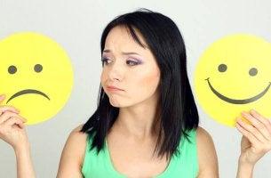 Mujer con emoticono triste y emoticono alegre