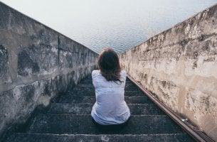 Mujer mirando al mar sentada en una escalera