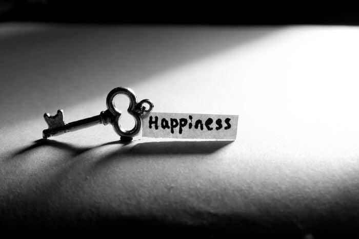 Llave con una hoja escrita con la palabra felicidad en inglés