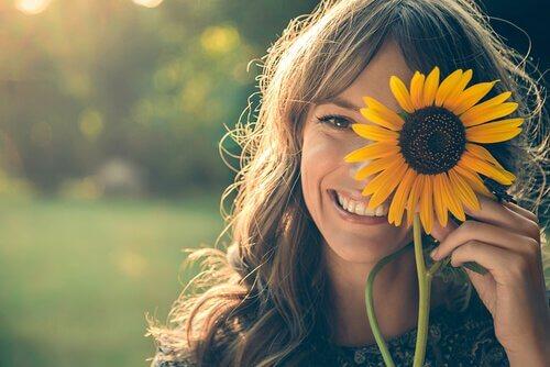 Mujer que sonríe con alegría y un girasol en la mano