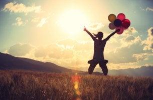 Mujer con globos saltando pensando en atreverse a hacer realidad sus sueños