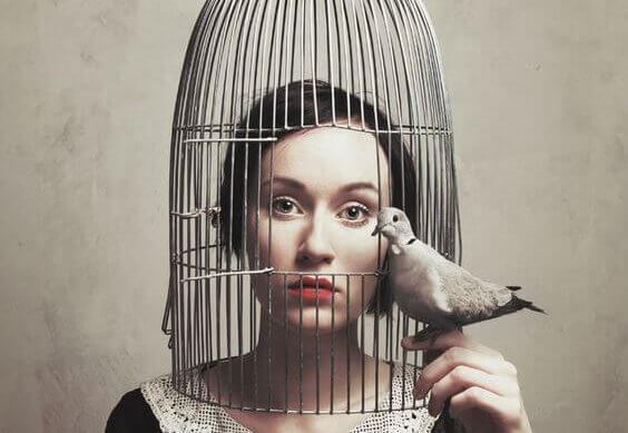 Mujer con la cabeza metida en una jaula