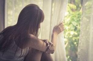 Mujer mirándose por la ventana