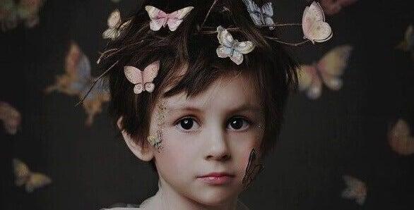 Niño con mariposas en la cabeza
