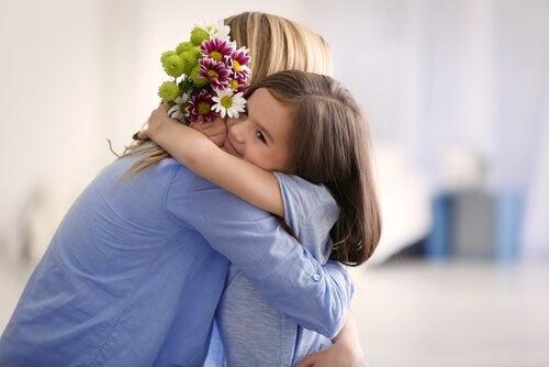 Madre e hija abrazadas con flores