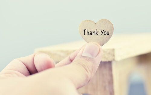 Mano sujetando un corazón con la palabra gracias