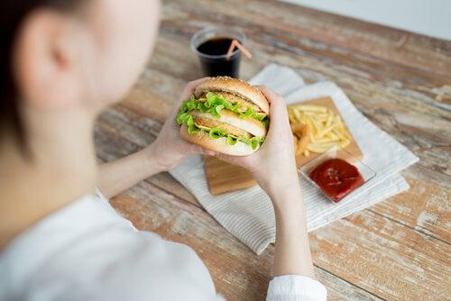 Mujer comiendo una hamburguesa por problemas de alimentación emocional