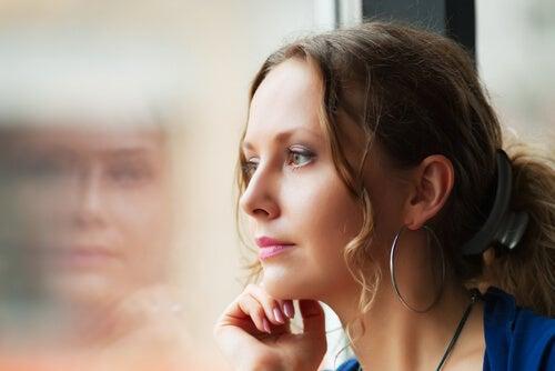 Mujer mirando por la ventana pensando en su educación