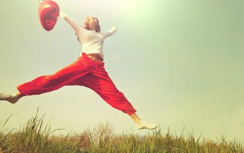 Mujer saltando con un globo rojo