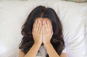 Mujer tapándose la cara preocupada