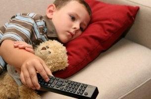 Niño viendo la tv con el mando