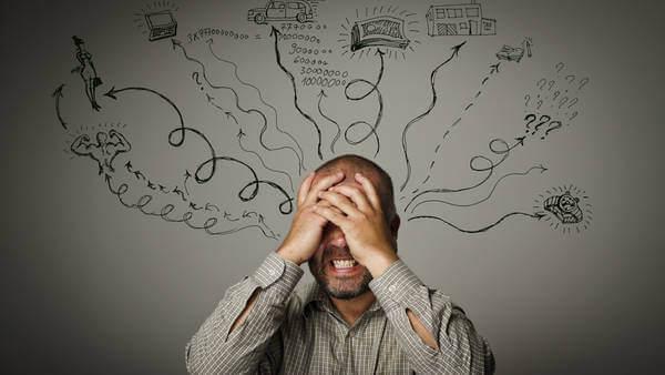 Hombre con las manos en la cabeza por estrés crónico