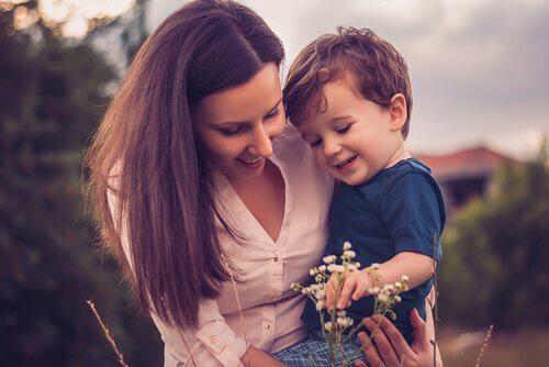 Madre con su hijo en brazos mirando una flor
