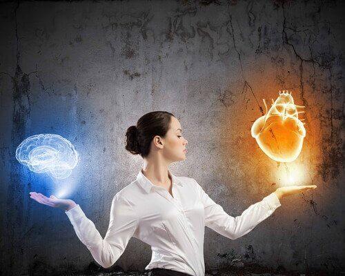 Mujer sosteniendo un corazón en una mano y un cerebro en otra