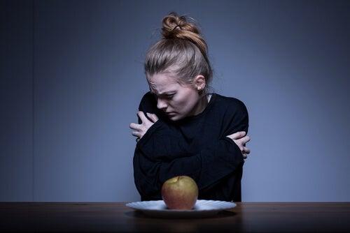 Chica con anorexia frente a una manzana