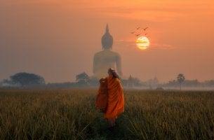 Hombre caminando con la figura de buda de espaldas en el horizonte