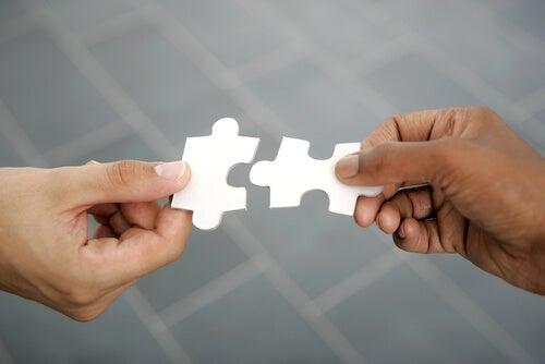 Manos con dos piezas de puzzle