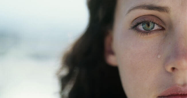 Mujer con una lágrima sobre su rostro pensando en sus días tristes
