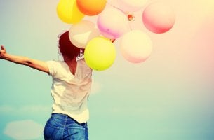 Mujer feliz sujetando globos de colores