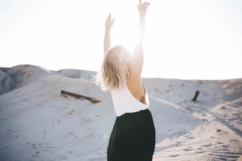 Mujer levantando las manos pensando en su personalidad