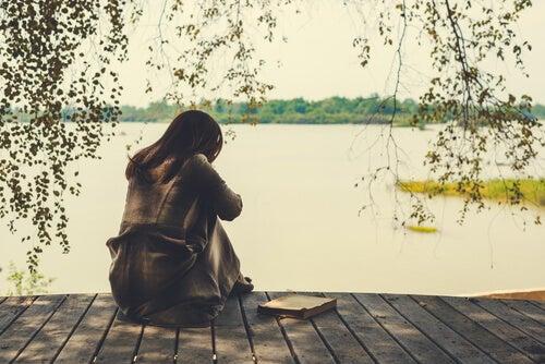 Mujer triste pensando en los cambios de su vida en el lago