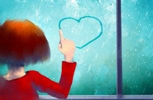 Niña dibujando un corazón en el cristal