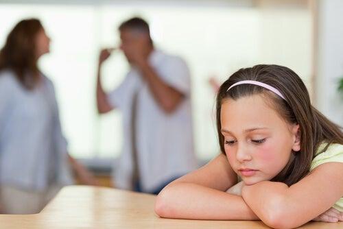 Niña escuchando a sus padres discutir por la falta de asertividad