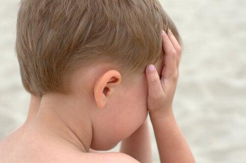 Niño triste con las manos en la cara