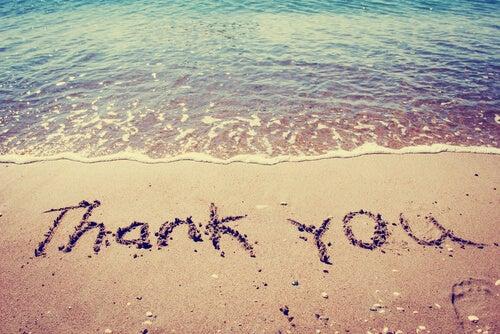 Gracias escrito en la arena de la playa en inglés