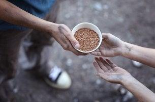 Hombre dando comida a una persona pobre