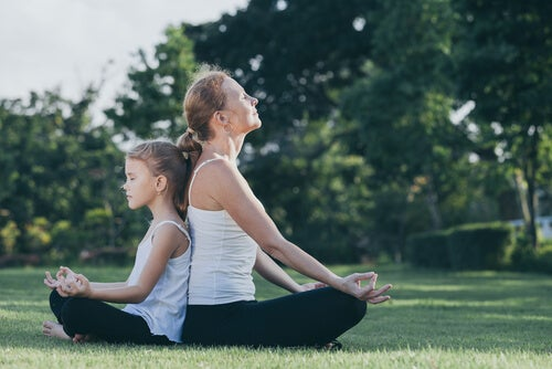mother and daughter meditating in the open