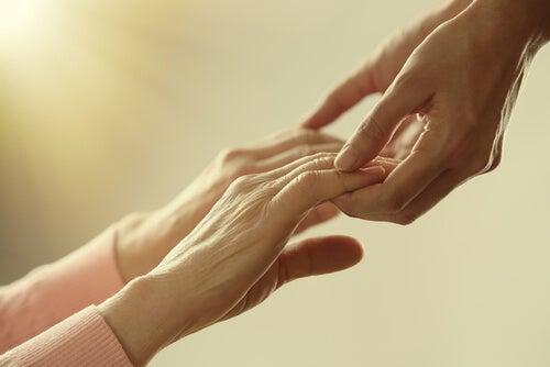 Manos de un adulto cogiendo las de una persona mayor para ayudarla