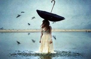 Mujer con un paraguas al reves en la cabeza