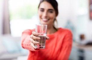 Mujer enseñando un vaso medio lleno