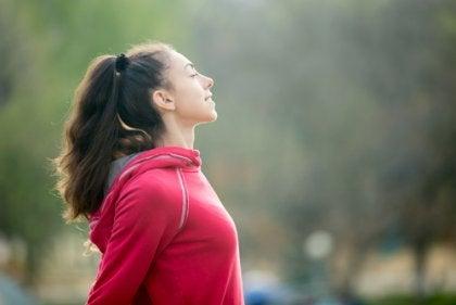 Mujer deportista con los ojos cerrados haciendo ejercicio físico
