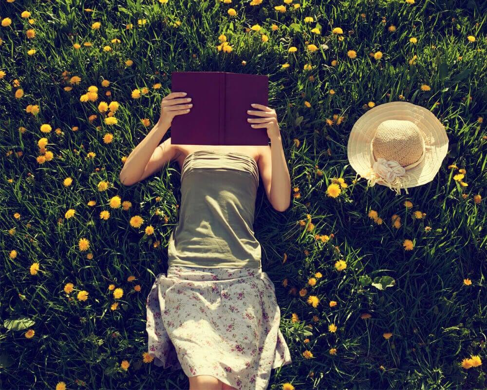 Mujer leyendo acostada sobre un jardín