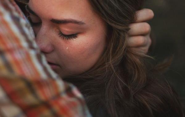 Mujer llorando abrazada a su pareja por dependencia emocional