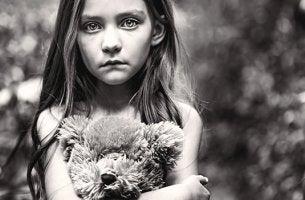 niña triste abrazada a su osito simbolizando el hijo olvidado