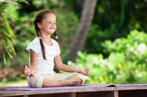 Niña haciendo meditación en el jardín